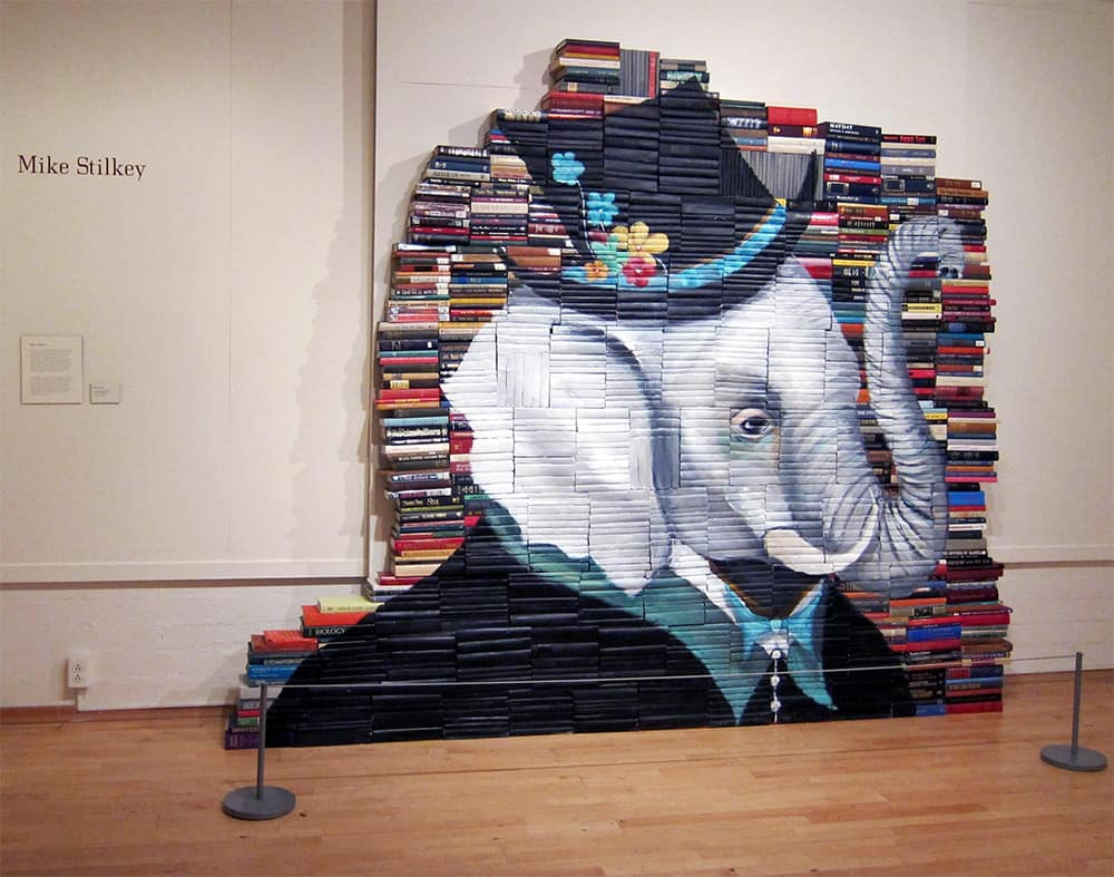 Mike Stilkey stack of books with paintings